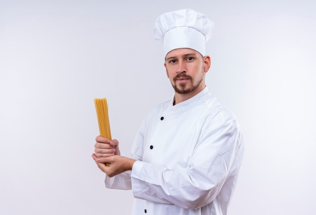 Cocinero cocinero profesional masculino en uniforme blanco y sombrero del cocinero que sostiene la pasta cruda del espagueti que mira confiada que se coloca sobre el fondo blanco