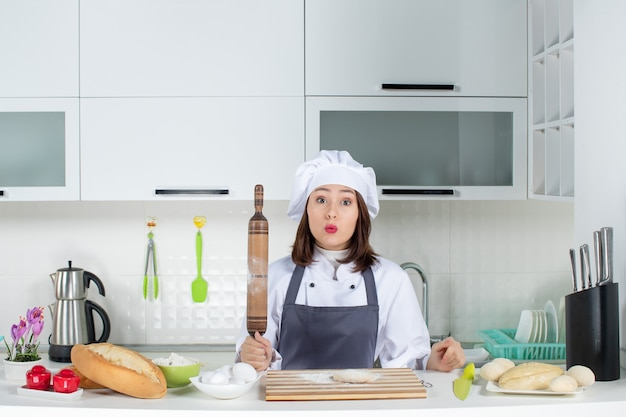 Cocinero de comis femenino sorprendido en uniforme de pie detrás de la mesa preparando pasteles en la cocina blanca