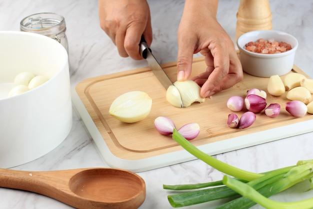 El cocinero cortando y picando la cebolla sobre una tabla de cortar de madera
