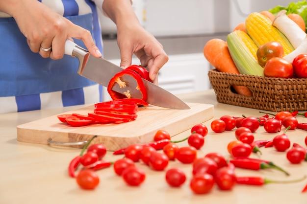 El cocinero en delantal azul corta las verduras. el concepto de productos ecológicos para cocinar.