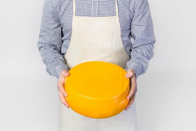 El cocinero en un delantal sostiene una cabeza de queso, queso holandés.