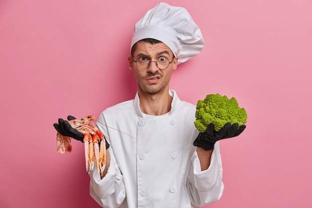 Cocinero disgustado con uniforme blanco, trabaja en un restaurante, se le asignó la tarea de cocinar un plato de brócoli y cangrejos de río, usa guantes negros