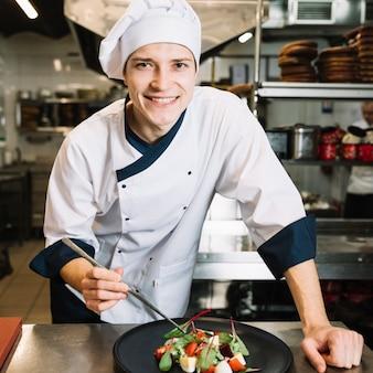 Cocinero feliz poniendo espinacas en un plato con ensalada