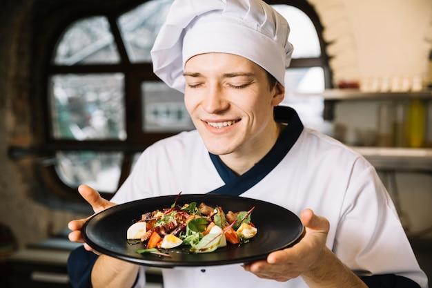 Cocinero feliz que huele la ensalada con carne en un plato