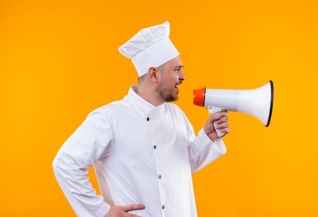 Cocinero guapo joven en uniforme de chef hablando por altavoz aislado en espacio naranja