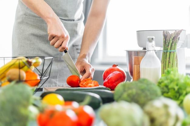 Cocinero del hombre joven que cocina la ensalada sana