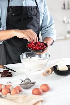 Un cocinero con huevos en una cocina rústica con el trasfondo de las manos de los hombres