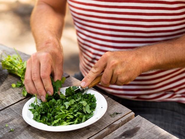 Cocinero irreconocible cortando apio para ensalada
