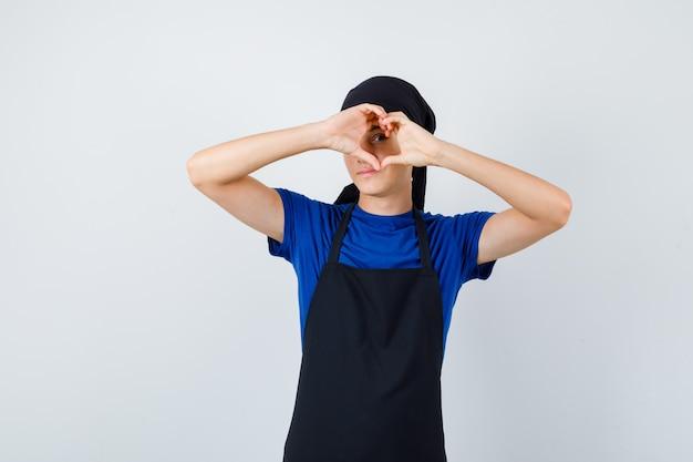 Cocinero joven que muestra el gesto del corazón en el ojo en camiseta, delantal y que parece curioso. vista frontal.