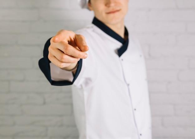 Cocinero joven que señala el dedo en el espectador