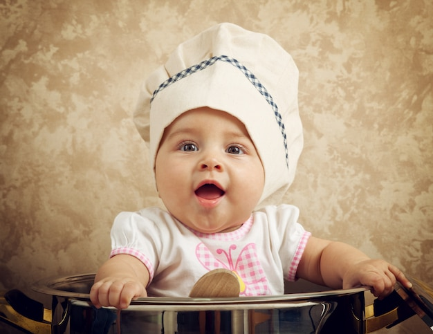 Cocinero lindo bebé en un caldero enorme