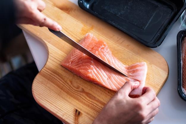 Cocinero de la mano que usa salmón crudo de la rebanada del cuchillo en la tajadera