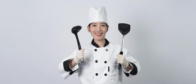 Cocinero de mediana edad mujer asiática sosteniendo utensilios de cocina