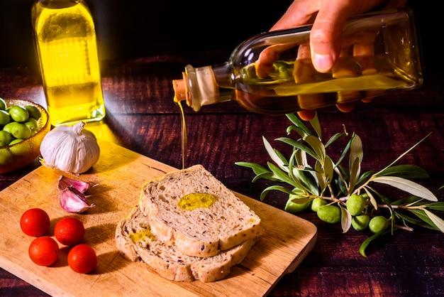 Un cocinero mediterráneo prepara una rebanada de pan con aceite de oliva virgen, tomates y ajo, un desayuno tradicional en los países mediterráneos.