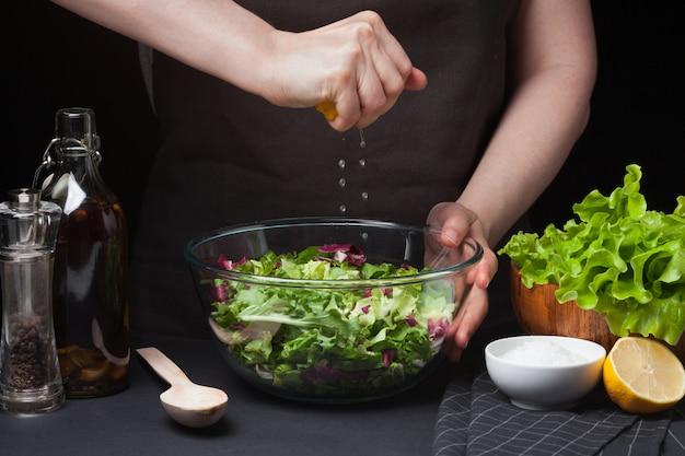 Cocinero de la mujer en la cocina que prepara la ensalada.