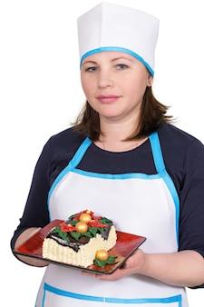 Cocinero de mujer sosteniendo un pastel de navidad