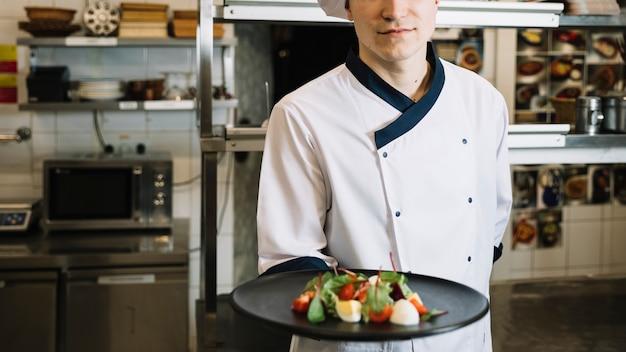 Cocinero con plato de ensalada vegetariana.