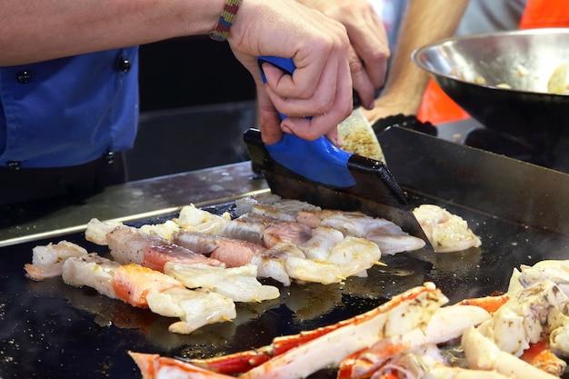 El cocinero prepara en la estufa de la calle barbacoa de diferentes carnes de pescado
