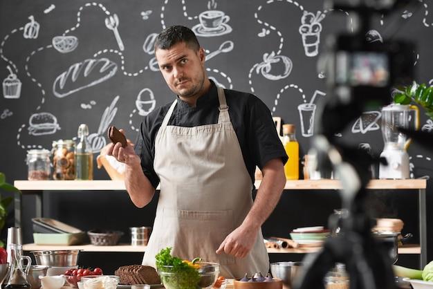 Cocinero profesional en delantal sosteniendo pan y mostrando una clase magistral de cocina
