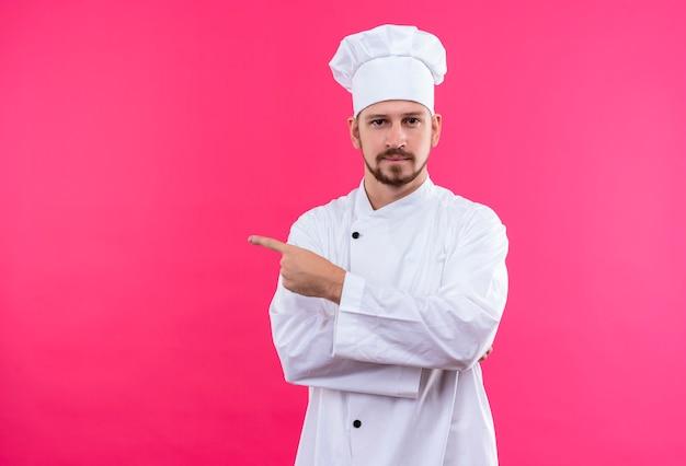 Cocinero profesional de sexo masculino en uniforme blanco y sombrero de cocinero apuntando con el dedo hacia el lado mirando a la cámara con expresión segura de pie sobre fondo rosa