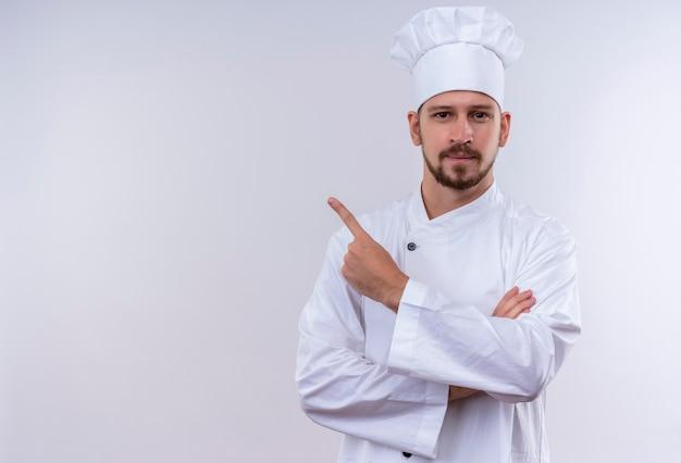 Cocinero profesional de sexo masculino en uniforme blanco y sombrero de cocinero apuntando hacia el lado con el dedo índice mirando confiado de pie sobre fondo blanco