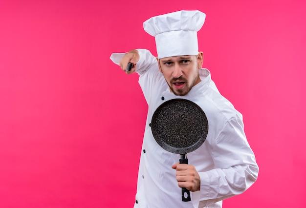 Cocinero profesional de sexo masculino en uniforme blanco y sombrero de cocinero sosteniendo una sartén y un cuchillo mirando a la cámara amenazando con un cuchillo de pie sobre fondo rosa