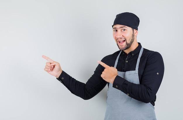 Cocinero de sexo masculino en camisa, delantal apuntando hacia afuera y mirando alegre, vista frontal.