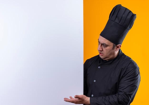 Cocinero de sexo masculino de mediana edad confundido en uniforme del cocinero que mira la pared del ápice en la pared amarilla con espacio de copia