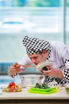 Cocinero de sexo masculino que prepara la comida en la cocina