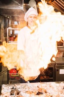 Cocinero de sexo masculino que sostiene la cacerola ardiente en la mano