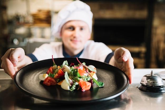 Cocinero sosteniendo un plato con ensalada cerca de la campana de servicio