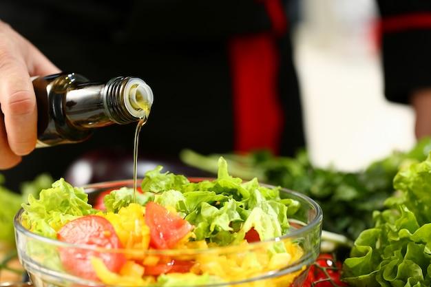 El cocinero sostiene la botella en la mano y gotea aceituna