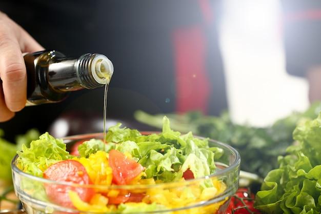 El cocinero sostiene la botella en la mano y gotea oliva