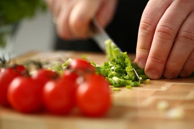 El cocinero sostiene el cuchillo en la mano y corta