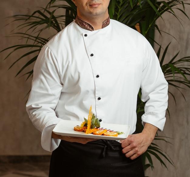 El cocinero sostiene los rollos rebanados en la placa