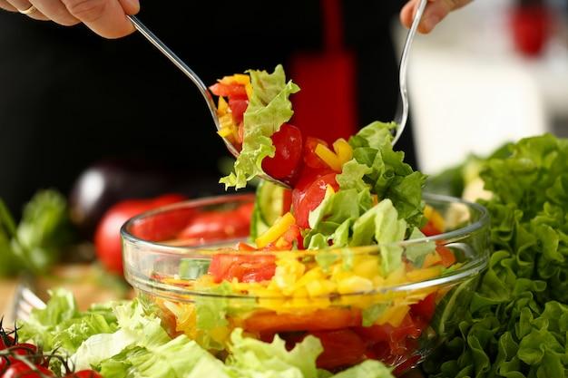 El cocinero sostiene el tenedor en la mano y mezcla