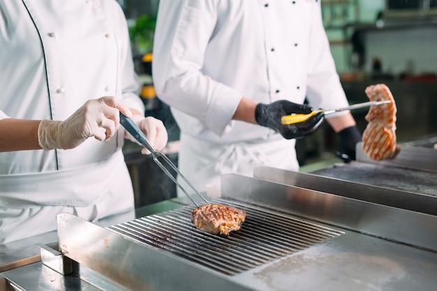 Los cocineros asan carne en la estufa en la cocina de un restaurante u hotel.