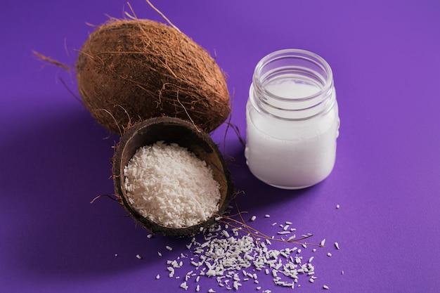 Coco, copos de coco y aceite de coco en tarro sobre fondo morado. concepto de cocina saludable