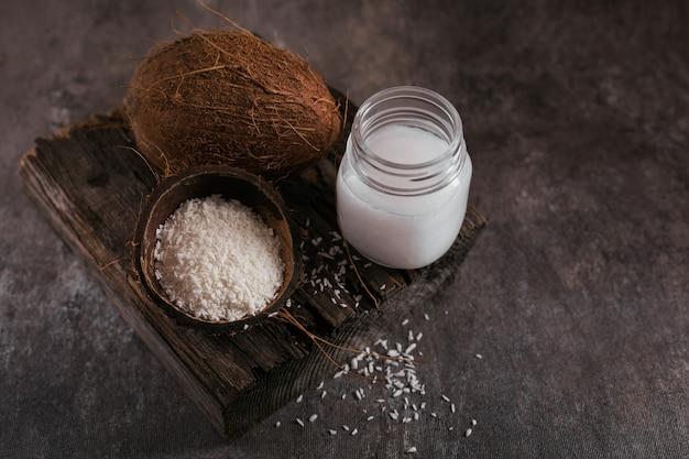 Coco, copos de coco y aceite de coco en tarro sobre mesa oscura. concepto de cocina saludable