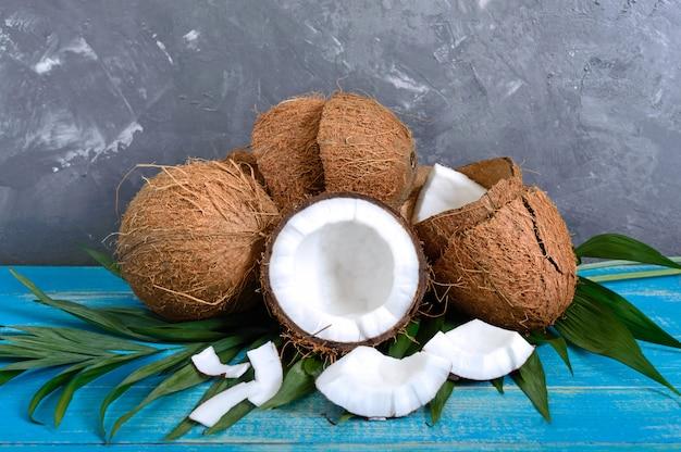 Coco entero, cáscara, hojas de palma verde sobre un fondo de madera azul. copia espacio fondo tropical
