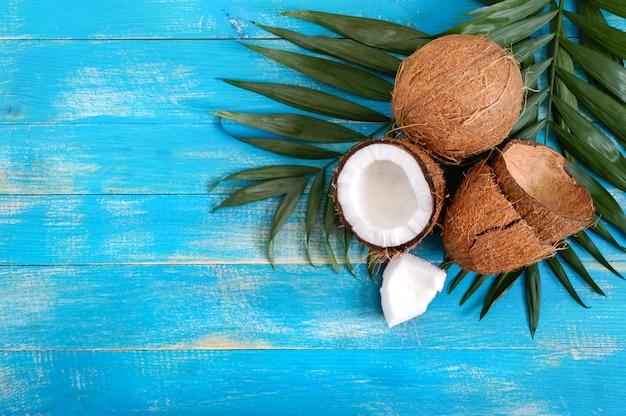 Coco entero, cáscara, hojas de palma verde sobre un fondo de madera azul. copia espacio vista superior, endecha plana. fondo tropical