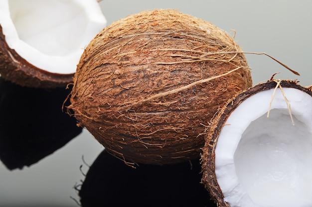 Coco fresco entero y picado en dos mitades sobre un fondo gris