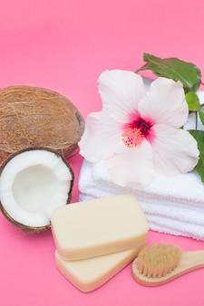 Coco; jabón; cepillo; flores y toallas en superficie rosa.