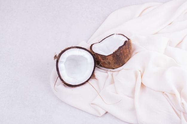 Un coco marrón cortado en dos pedazos sobre una toalla blanca.