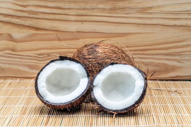 Coco medio cortado maduro en un fondo de madera