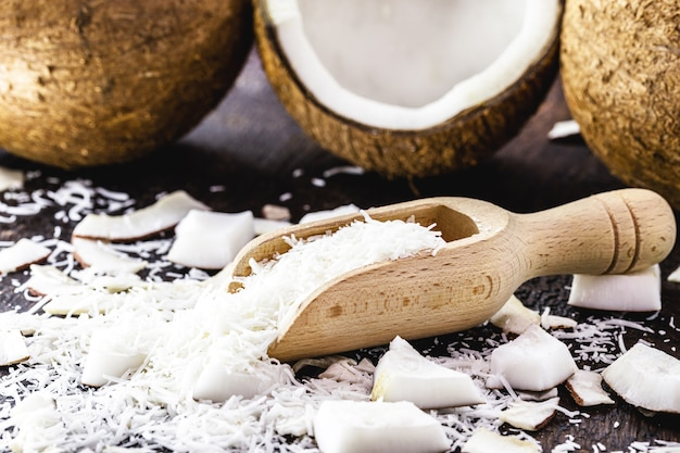 Coco rallado en cuchara medidora de madera, porción de coco en rodajas, ingrediente de caramelo