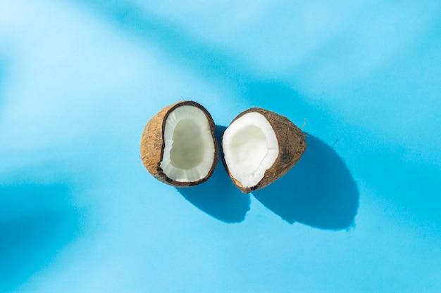 Coco roto en una superficie azul bajo luz natural con sombras. luz dura. concepto de dieta, alimentación saludable, descanso en los trópicos, vacaciones y viajes, vitaminas. vista plana, vista superior.