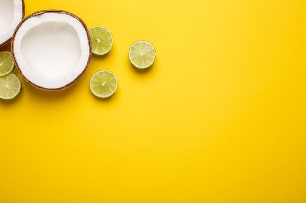 Coco tropical, palmera y lima sobre un amarillo.