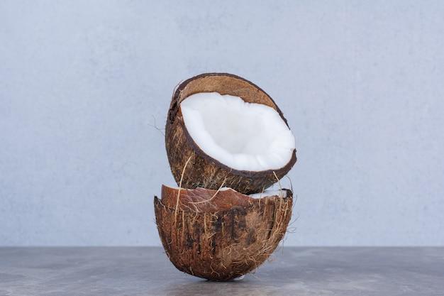 Cocos frescos medio cortados en la mesa de piedra.