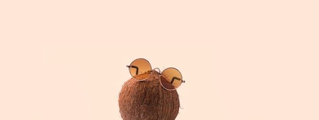Los cocos llevan gafas de sol sobre fondo rosa. concepto de vacaciones en los trópicos soleados